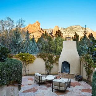 Esempio di un patio o portico american style con nessuna copertura e un caminetto