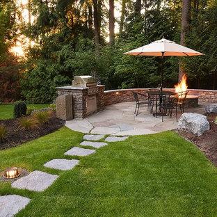 Ispirazione per un grande patio o portico tradizionale dietro casa con un focolare e pavimentazioni in pietra naturale