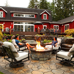 Example of a mountain style backyard stone patio design in Seattle with a fire pit