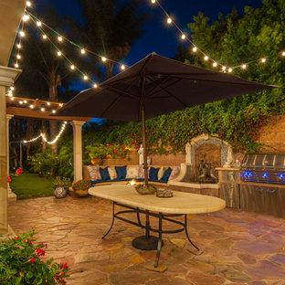 Patio kitchen - mediterranean stone patio kitchen idea in Los Angeles with no cover