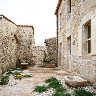Idee per un patio o portico mediterraneo di medie dimensioni e nel cortile laterale con pavimentazioni in pietra naturale e nessuna copertura