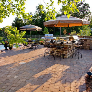 Photo of a large traditional back patio in Other with a water feature, natural stone paving and an awning.