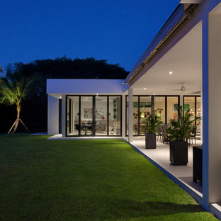 This is an example of an expansive midcentury courtyard patio in Miami with a roof extension.