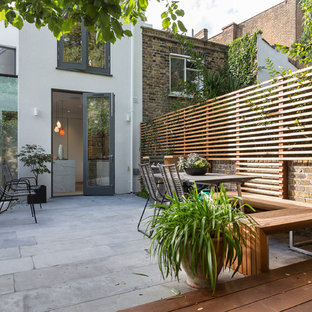 This is an example of a medium sized contemporary back patio in London with concrete paving and no cover.