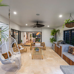 Design ideas for a beach style backyard patio in Gold Coast - Tweed with an outdoor kitchen, natural stone pavers and a roof extension.