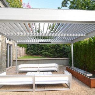 Esempio di un patio o portico minimal di medie dimensioni e dietro casa con graniglia di granito e una pergola