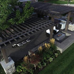 Esempio di un patio o portico minimal di medie dimensioni e dietro casa con cemento stampato e una pergola