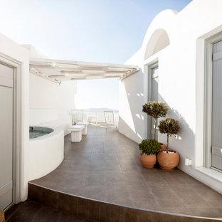 Foto de patio marinero, en patio, con suelo de baldosas y toldo
