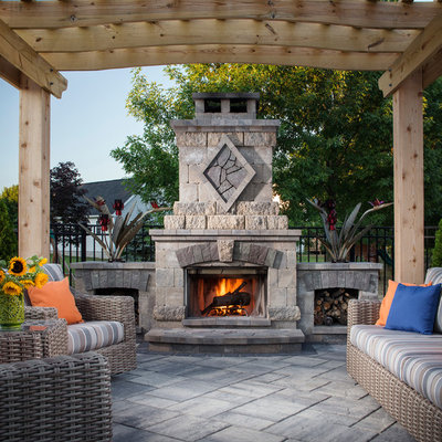 Inspiration for a mid-sized timeless backyard stone patio remodel in New York with a pergola and a fireplace