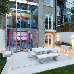 Large contemporary back patio in London with an outdoor kitchen and no cover.