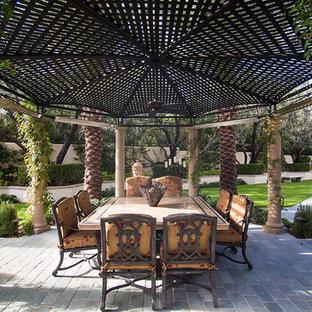 Foto di un grande patio o portico mediterraneo dietro casa con un focolare e un gazebo o capanno