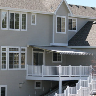 This is an example of a traditional back patio in Denver with decking and an awning.