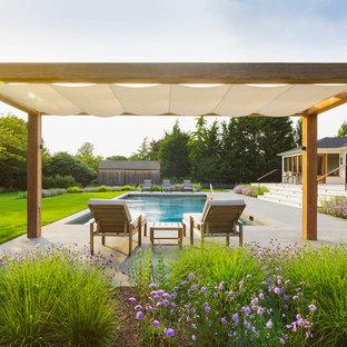 Ispirazione per un grande patio o portico country dietro casa con pavimentazioni in cemento e una pergola