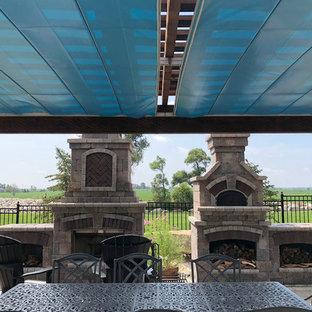 Immagine di un patio o portico american style dietro casa con un caminetto, pavimentazioni in pietra naturale e una pergola