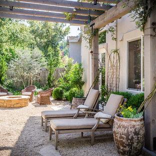 Cette image montre une terrasse arrière méditerranéenne avec un gravier de granite et une pergola.