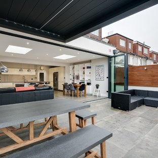 This is an example of a medium sized contemporary back patio in London with natural stone paving and an awning.