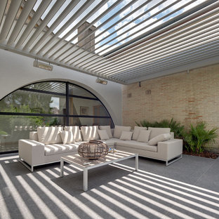 Design ideas for a contemporary courtyard patio in Buckinghamshire with a pergola.