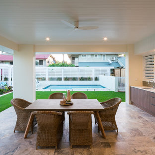 Photo of a large contemporary patio in Brisbane with an outdoor kitchen, tile and a roof extension.