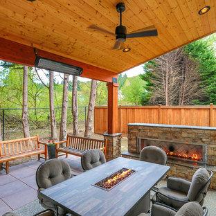 Immagine di un patio o portico stile americano di medie dimensioni e dietro casa con un caminetto, pavimentazioni in cemento e un tetto a sbalzo