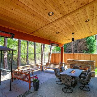 Immagine di un patio o portico american style di medie dimensioni e dietro casa con un caminetto, pavimentazioni in cemento e un tetto a sbalzo