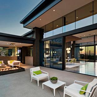 Esempio di un ampio patio o portico minimalista dietro casa con un focolare, lastre di cemento e un tetto a sbalzo