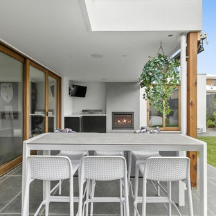 Large contemporary backyard patio in Geelong with with fireplace, tile and a roof extension.