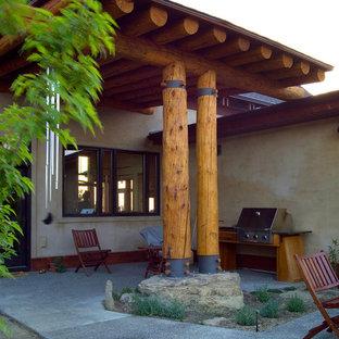 Immagine di un patio o portico etnico di medie dimensioni e in cortile con lastre di cemento e un parasole