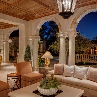 Cette image montre une très grande terrasse arrière traditionnelle avec des pavés en pierre naturelle et une extension de toiture.