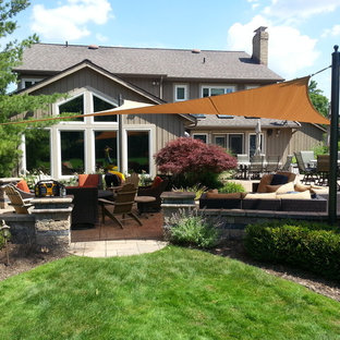 Photo of a large contemporary back patio in Cleveland with an outdoor kitchen, stamped concrete and an awning.