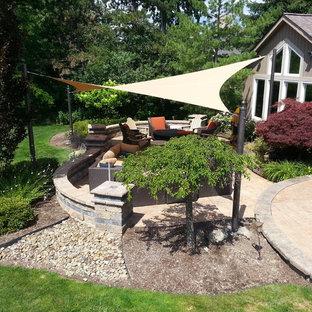Esempio di un patio o portico chic di medie dimensioni e dietro casa con pavimentazioni in cemento e un parasole
