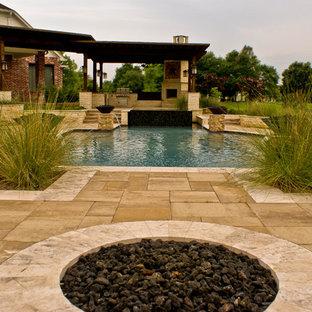 Immagine di un ampio patio o portico tradizionale dietro casa con un focolare, piastrelle e nessuna copertura