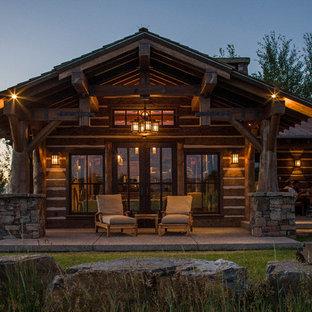 Inspiration pour une terrasse arrière chalet de taille moyenne avec une dalle de béton, une extension de toiture et un foyer extérieur.