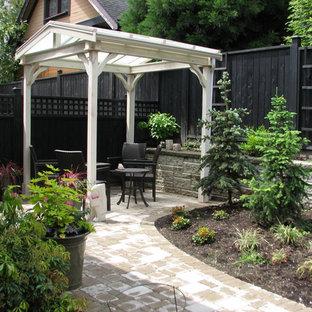 Ejemplo de patio tradicional, pequeño, en patio trasero, con jardín de macetas, adoquines de hormigón y pérgola