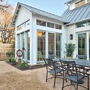 This is an example of a large traditional front patio in Austin with no cover and decomposed granite.