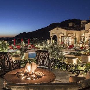 Foto di un ampio patio o portico mediterraneo dietro casa con pavimentazioni in pietra naturale e un gazebo o capanno