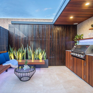 Photo of a small contemporary patio in Sydney with a roof extension.