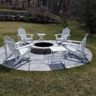 Esempio di un piccolo patio o portico country dietro casa con un focolare e cemento stampato
