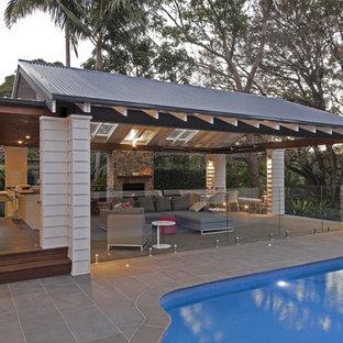Idee per un grande patio o portico contemporaneo dietro casa con un focolare e un gazebo o capanno