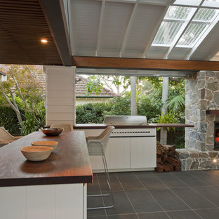 Example of a large trendy backyard patio design in Sydney with a fire pit and a pergola