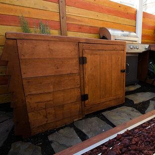 Immagine di un piccolo patio o portico american style dietro casa con un focolare, pavimentazioni in pietra naturale e un parasole