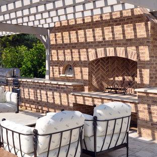 Immagine di un ampio patio o portico bohémian nel cortile laterale con pavimentazioni in pietra naturale e una pergola