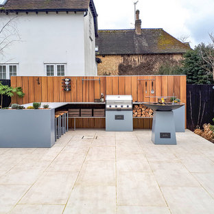 Photo of a medium sized contemporary back patio in Kent with an outdoor kitchen, no cover and natural stone paving.