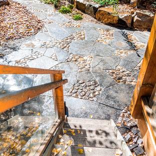 Cette photo montre une petite terrasse arrière romantique avec un foyer extérieur, des pavés en pierre naturelle et aucune couverture.