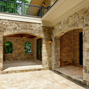 Example of a huge minimalist backyard stone patio design in DC Metro with no cover