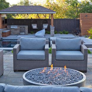 Ejemplo de patio minimalista, grande, en patio trasero, con brasero, adoquines de hormigón y cenador
