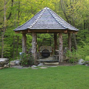 Inspiration for a rustic stone patio remodel in New York with a gazebo