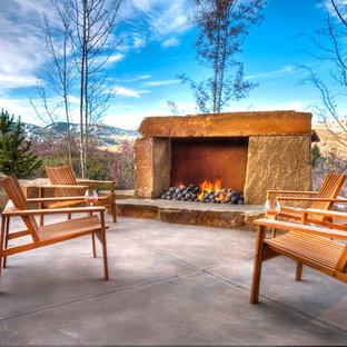 Ejemplo de patio rural, de tamaño medio, sin cubierta, en patio trasero, con losas de hormigón y chimenea