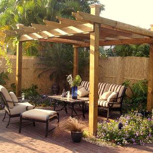 Ispirazione per un piccolo patio o portico stile rurale dietro casa con un giardino in vaso, pavimentazioni in mattoni e una pergola