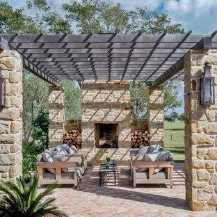 Ispirazione per un grande patio o portico country dietro casa con pavimentazioni in mattoni, una pergola e un caminetto