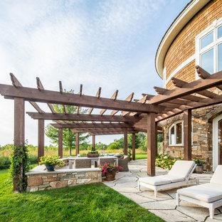 На фото: большая пергола во дворе частного дома на заднем дворе в стиле рустика с покрытием из каменной брусчатки